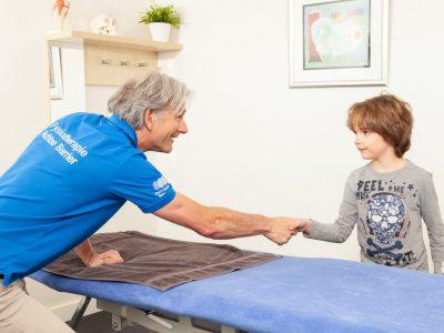 Fysiotherapeut geeft jonge client een hand.